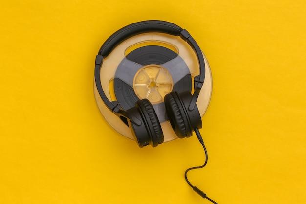 Fones de ouvido estéreo e bobina magnética de áudio em fundo amarelo. vista do topo