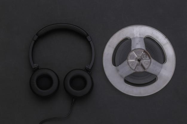 Fones de ouvido estéreo e bobina magnética de áudio em fundo preto. vista do topo