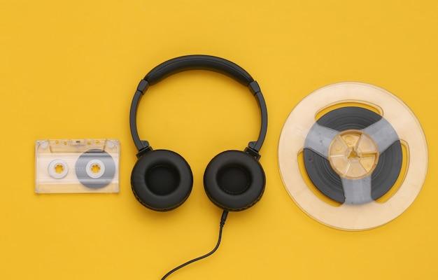 Fones de ouvido estéreo e bobina magnética de áudio, fita cassete em fundo amarelo. vista do topo. postura plana