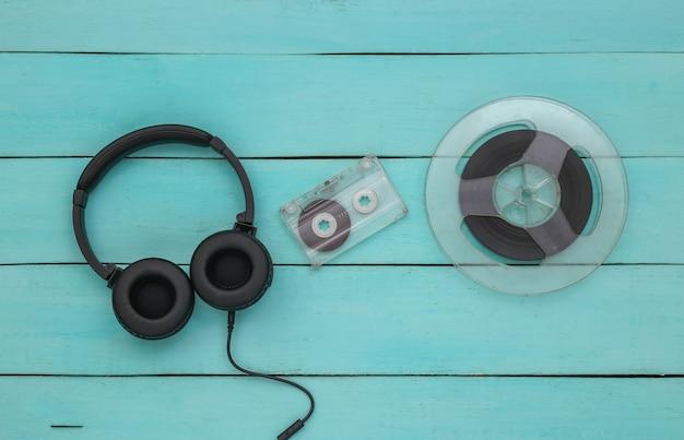Fones de ouvido estéreo e bobina magnética de áudio, fita cassete em fundo azul de madeira. vista do topo