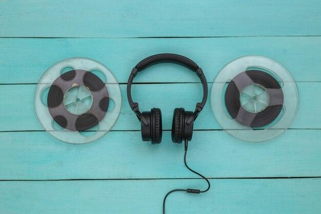 Fones de ouvido estéreo e bobina magnética de áudio sobre fundo azul de madeira. vista do topo