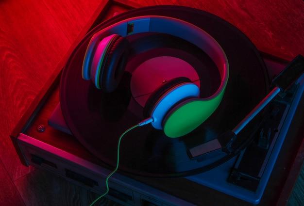 Fones de ouvido estéreo e toca-discos de vinil retrô em piso de madeira com luz de néon vermelho-azulada