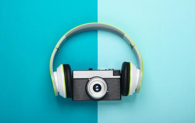 Fones de ouvido estéreo elegantes com câmera retro na superfície azul