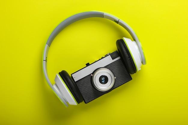 Fones de ouvido estéreo elegantes com fio com câmera retro em superfície verde