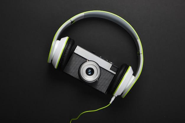 Fones de ouvido estéreo elegantes com fio com câmera retro na superfície preta
