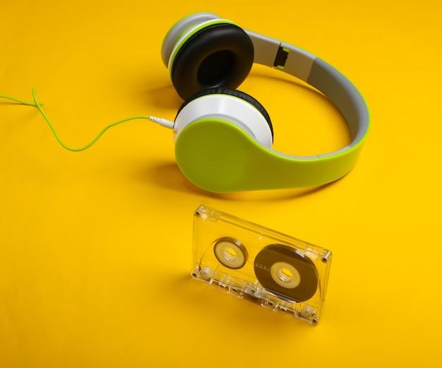 Fones de ouvido estéreo elegantes com fio com fita cassete na superfície amarela