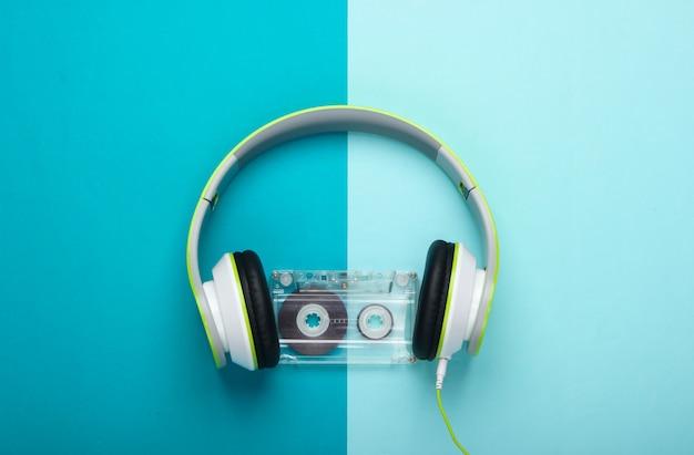 Fones de ouvido estéreo elegantes com fio com fita cassete na superfície azul