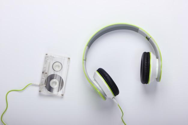 Fones de ouvido estéreo elegantes com fio com fita cassete na superfície branca