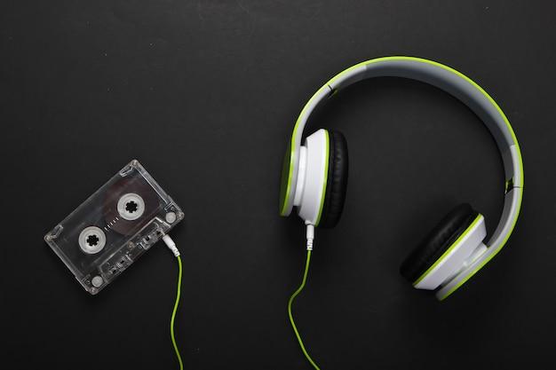 Fones de ouvido estéreo elegantes com fio com fita cassete na superfície preta