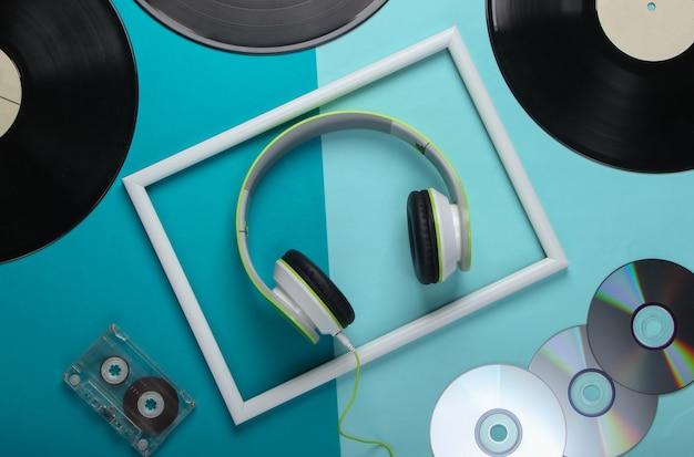 Fones de ouvido estéreo elegantes com moldura branca, discos de vinil, fita cassete e discos de cd na superfície azul
