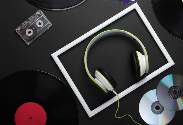 Fones de ouvido estéreo elegantes com moldura branca, discos de vinil, fita cassete e discos de cd na superfície preta
