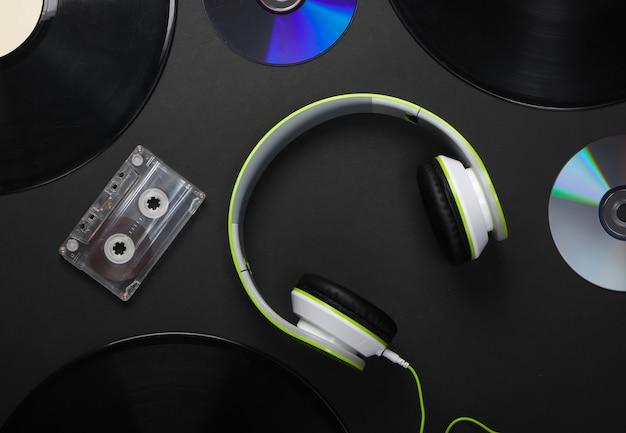 Fones de ouvido estéreo elegantes, discos de vinil, fita cassete e discos de cd na superfície preta