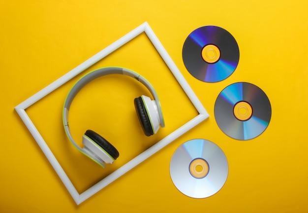 Fones de ouvido estéreo elegantes e discos de cd na superfície amarela com moldura branca