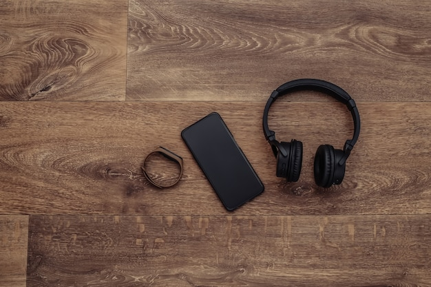 Fones de ouvido estéreo sem fio com smartphone, pulseira inteligente em um fundo de madeira. dispositivos modernos. vista do topo