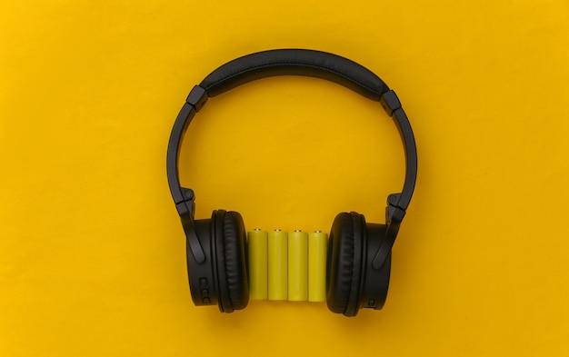 Fones de ouvido estéreo sem fio e quatro pilhas aa amarelas em fundo amarelo. vista do topo