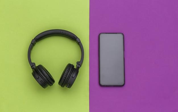 Fones de ouvido estéreo sem fio e smartphone em fundo roxo verde. vista do topo