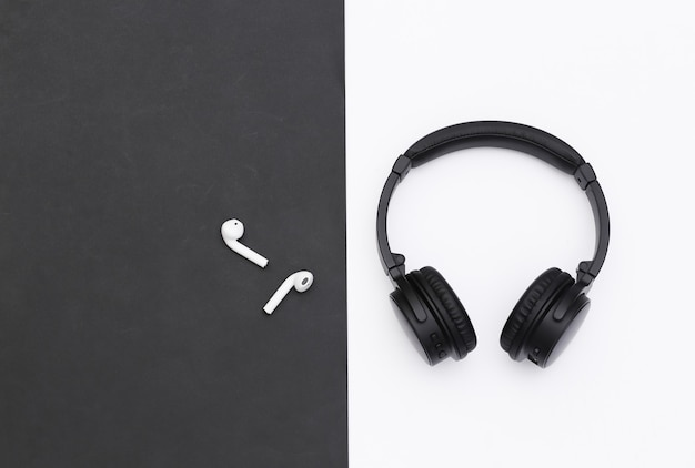 Fones de ouvido estéreo sem fio grandes e pequenos fones de ouvido em fundo preto e branco. vista do topo