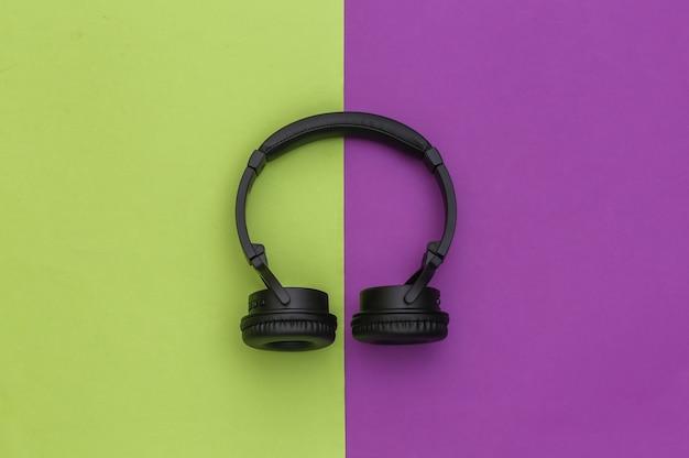 Fones de ouvido estéreo sem fio sobre fundo verde roxo. vista do topo