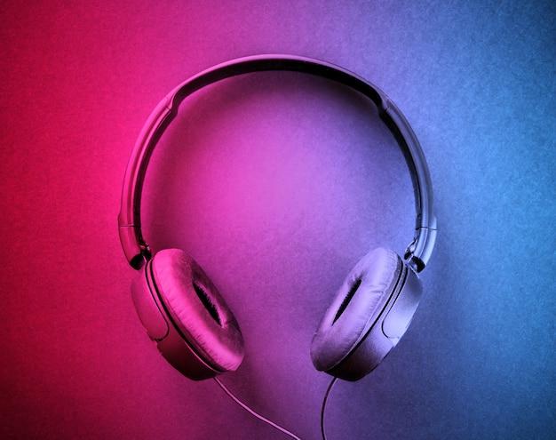 Fones de ouvido isolados em um fundo gradiente de rosa para azul