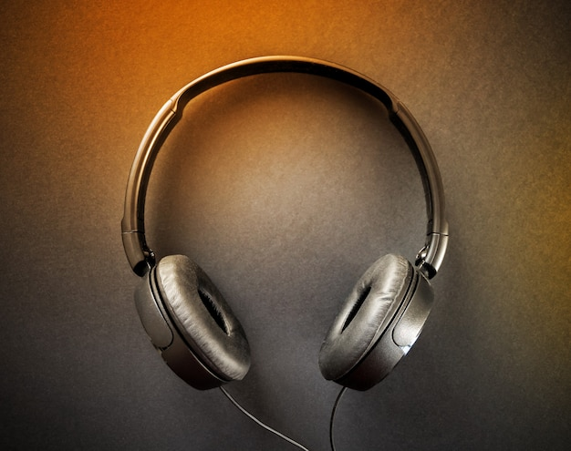 Fones de ouvido isolados em um fundo preto e laranja