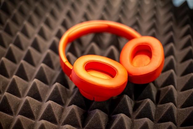 Fones de ouvido laranja para monitor sem fio sobre um painel de cancelamento de ruído de espuma escura