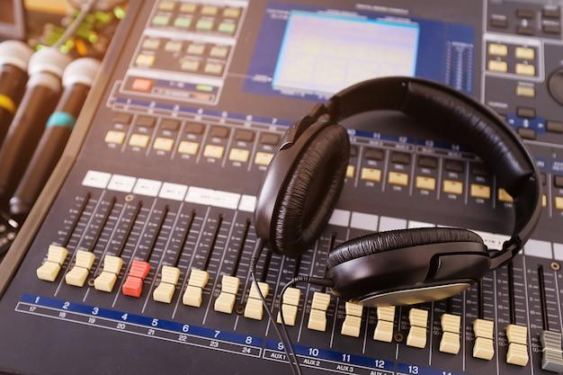 Fones de ouvido, microfones e equipamentos de amplificação nos botões e faders do mixer de áudio do studio.