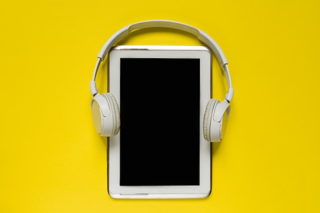 Fones de ouvido modernos brancos e tablet na tendência backgound amarelo plana leigos espaço de exibição superior para texto