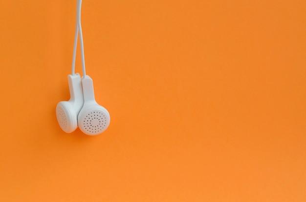 Fones de ouvido modernos brancos pendurado em um fundo laranja brilhante
