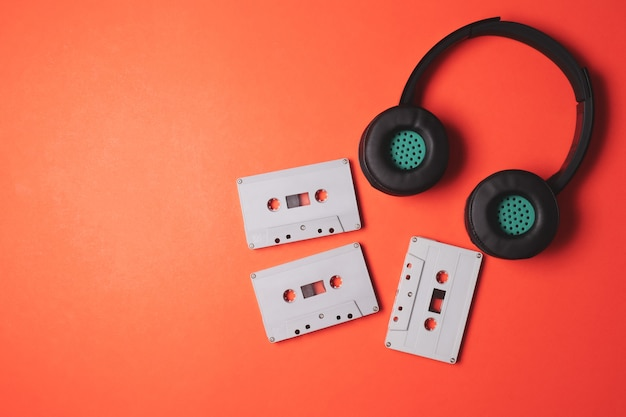 Fones de ouvido modernos com fitas cassete de áudio em um fundo laranja. espaço livre para o texto