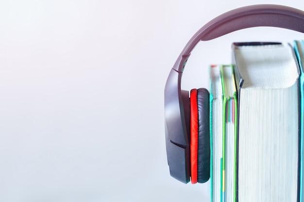 Fones de ouvido modernos e livros sobre a mesa no fundo branco. conceito de audiobook.