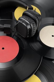 Fones de ouvido na pilha de diferentes discos de vinil com etiquetas em branco.