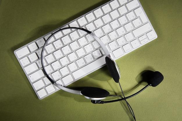 Fones de ouvido no teclado branco. conceito de serviço de suporte