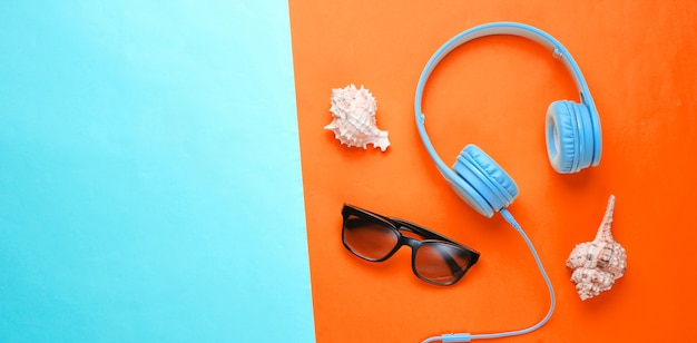 Fones de ouvido, óculos de sol e conchas isoladas