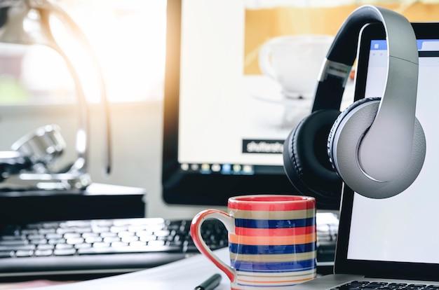 Fones de ouvido penduram no monitor do laptop com tela em branco.