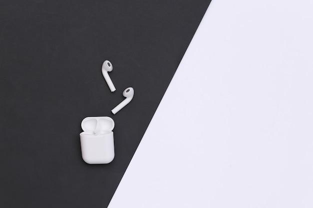 Fones de ouvido pequenos com estojo de carregador em fundo preto e branco. vista do topo. copie o espaço
