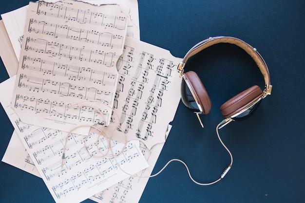 Fones de ouvido perto da pilha de partituras