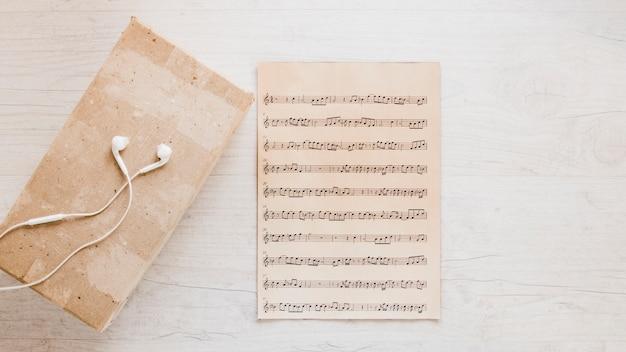Fones de ouvido perto de partituras antigas