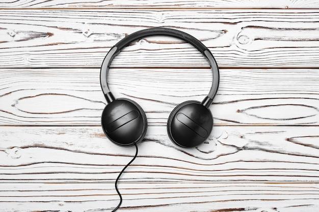 Fones de ouvido pretos com fio em fundo de madeira