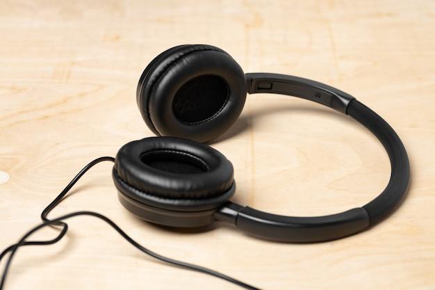 Fones de ouvido pretos com fio na superfície de madeira
