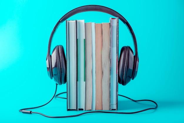 Fones de ouvido pretos com uma pilha de livros sobre um fundo azul.