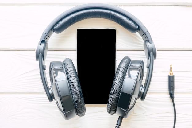 Fones de ouvido pretos e espaço de smartphone para texto