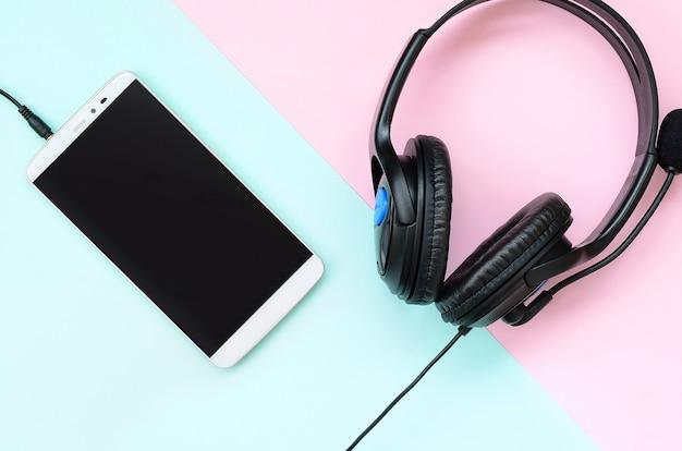 Fones de ouvido pretos e smartphone encontra-se em um fundo violeta pastel colorido
