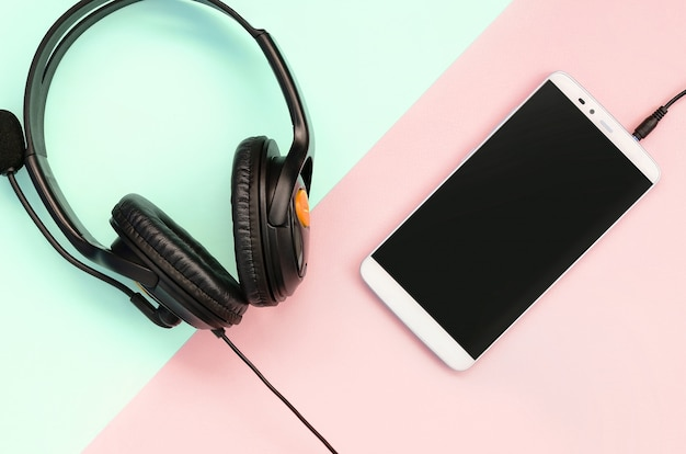 Fones de ouvido pretos e smartphone encontra-se em um rosa pastel colorido