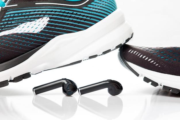 Fones de ouvido pretos e tênis pretos para corrida