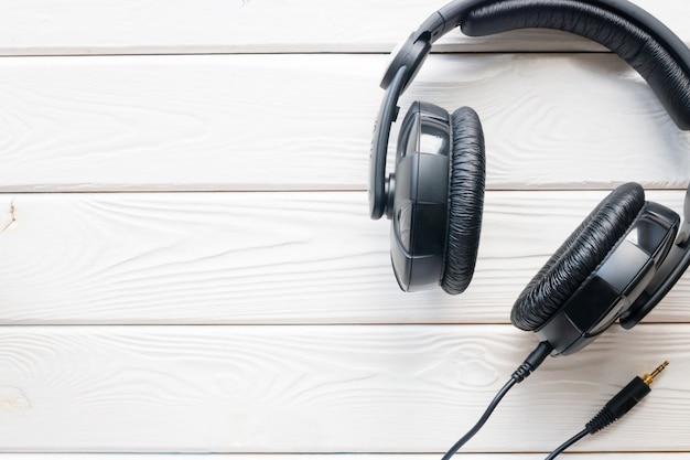 Fones de ouvido pretos em um fundo branco de madeira