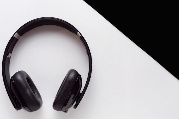 Fones de ouvido pretos grandes em um fundo branco, fones de ouvido brancos pequenos em uma vista superior do fundo preto com espaço de cópia de texto