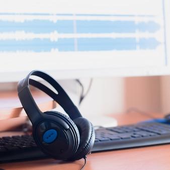 Fones de ouvido pretos grandes encontram-se na área de trabalho de madeira do designer de som