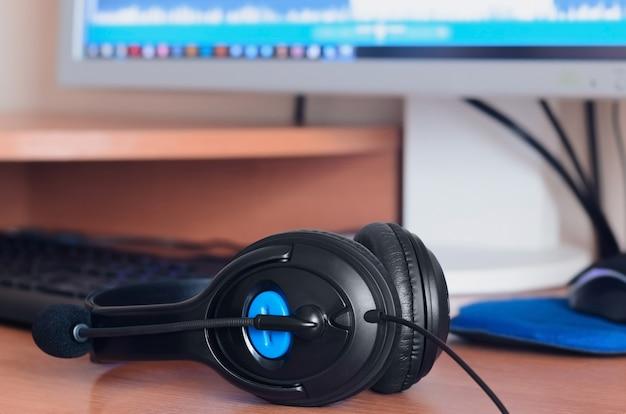 Fones de ouvido pretos grandes estão na área de trabalho de madeira do designer de som