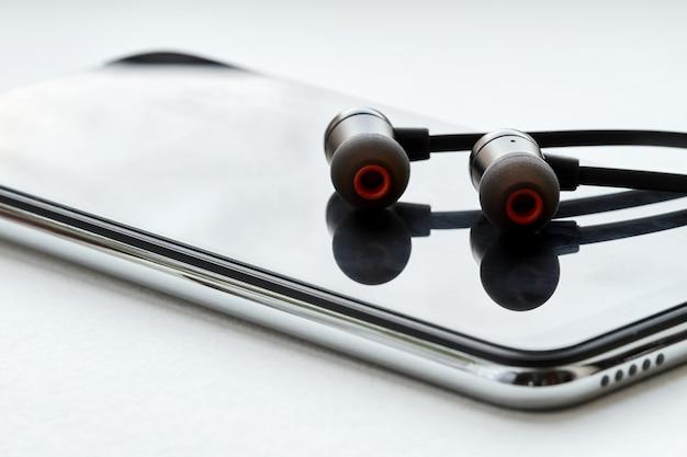 Fones de ouvido pretos mentem sobre o smartphone moderno. fundo branco, closeup
