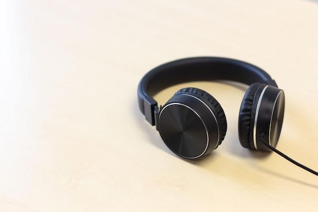 Fones de ouvido pretos no fundo da mesa de madeira